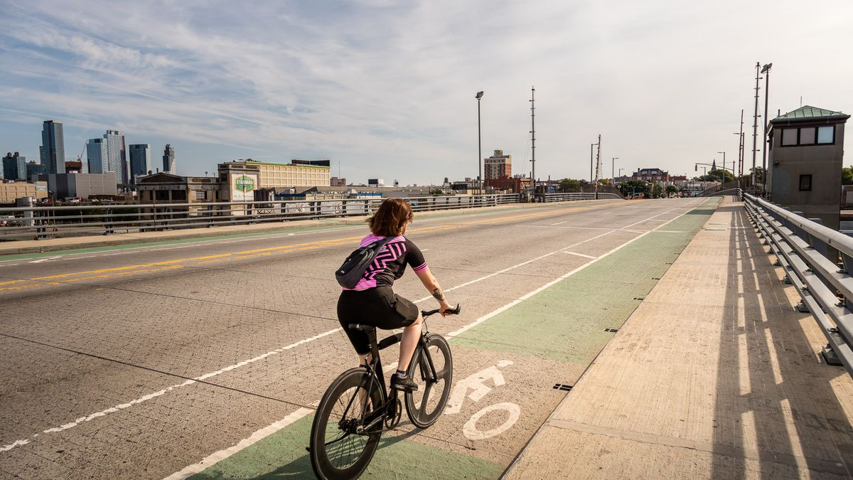 A woman in a black and pink shirt and black shorts rides a bike over a bridge in Brooklyn.