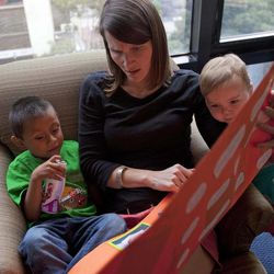 In this Thursday, Sept. 6, 2012 photo, Jessica Hooker, center, reads to her children; Daniel, left, and Ellyson, right, in Guatemala City. Daniel was 18 months old when the Tennessee couple Ryan and Jessica Hooker began the process to adopt him in Guatemala. They just got him at age 6. His is one of hundreds of adoption cases that were put in limbo five years ago, when the Guatemalan government declared a moratorium on international adoptions because of irregularities and fraud.