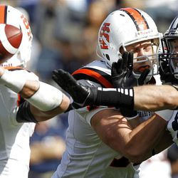 Idaho State Bengals quarterback Kevin Yost is pressured by Brigham Young Cougars linebacker Jadon Wagner, right, as Brigham Young University faces Idaho State in NCAA football in Provo, Saturday, Oct. 22, 2011. At center of photo is Erik Jacobsen of of ISU.