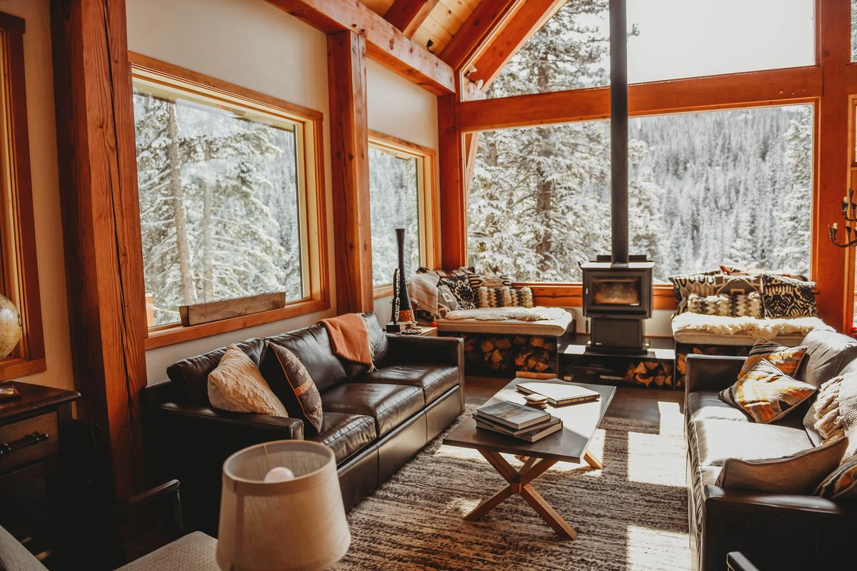 The interior of a cabin has large leather couches, a wood burning stove, and large picture windows that look out onto snowy trees.