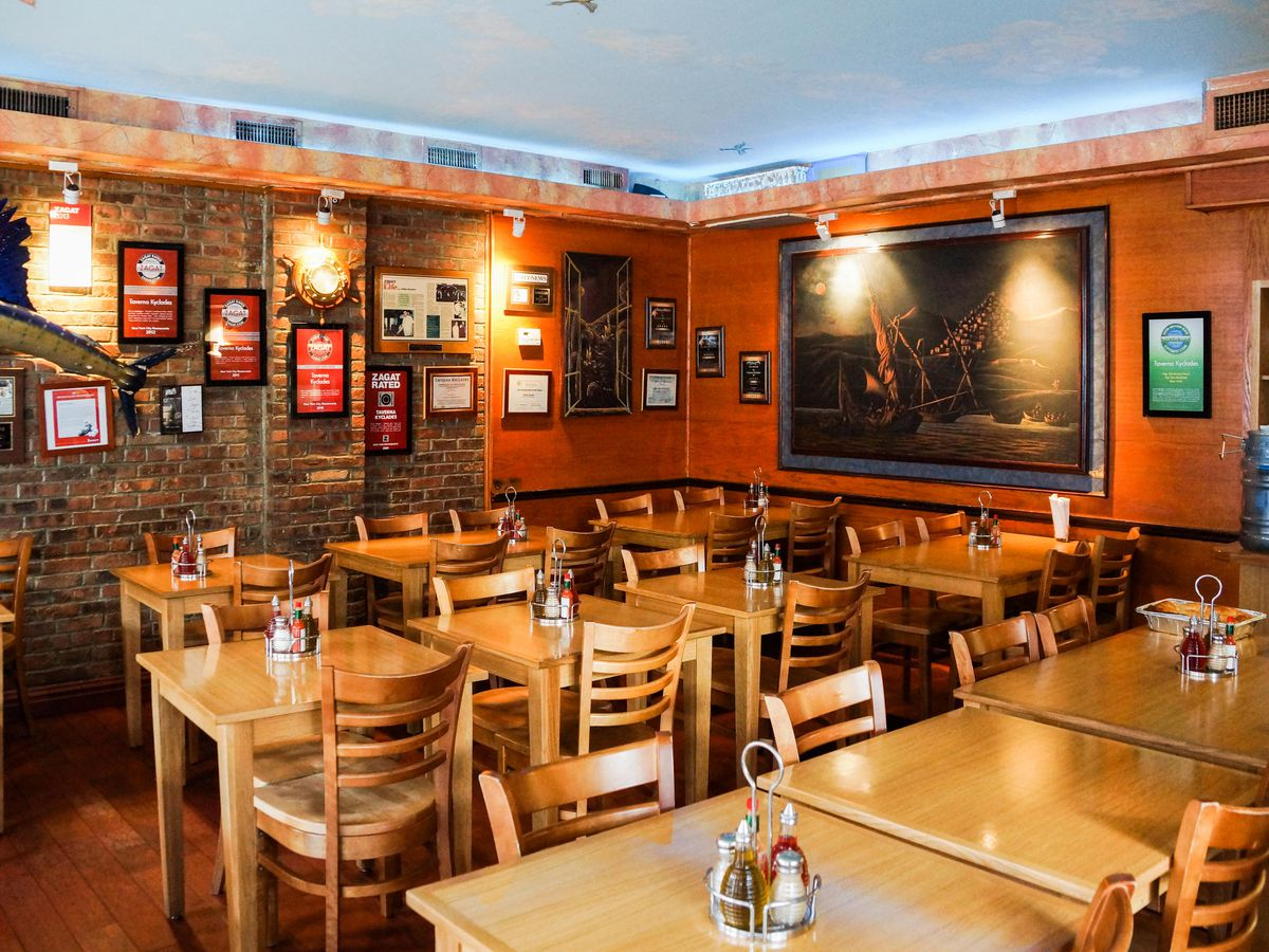The interior of Taverna Kyclades in Astoria with blond wood tables and exposed brick walls
