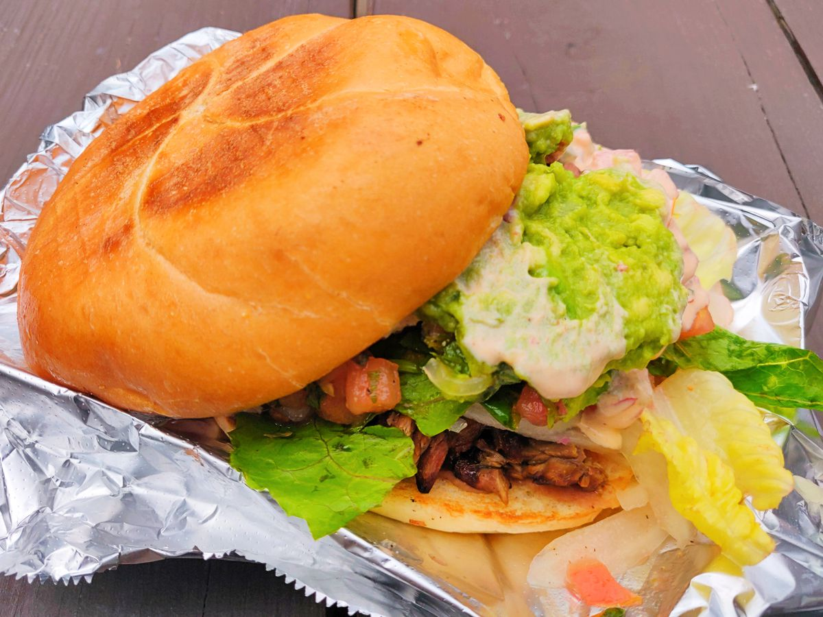 The top half of the bun of a Mexican torta is pushed back slightly from the sandwich, showing off ample fillings.