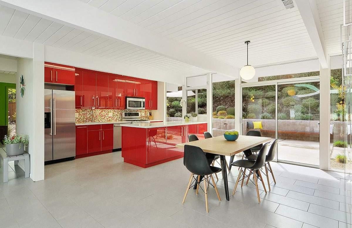 A midcentury kitchen with red cabinetry and light grey tiled floors. The ceiling is painted white wood. There is a table, chairs, and floor to ceiling windows.
