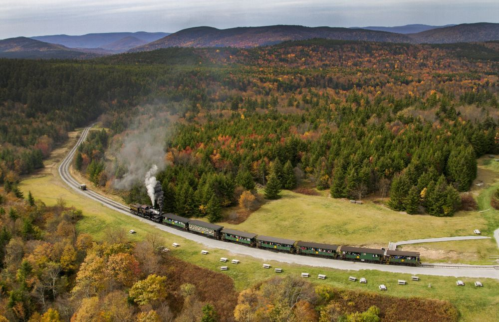 An aerial view of a train riding on a track through a countryside full of trees. There is smoke billowing from the train engine. There are mountains in the distance.