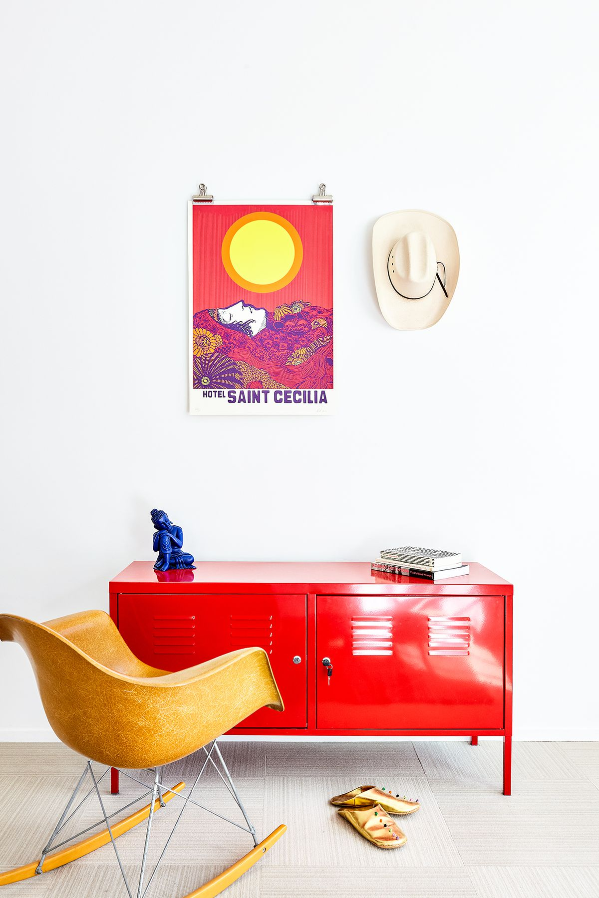 A bright red metal cabinet sits against a painted white wall. There is a brown chair next to it along with slippers. On the wall hangs a colorful art print and a cowboy hat.