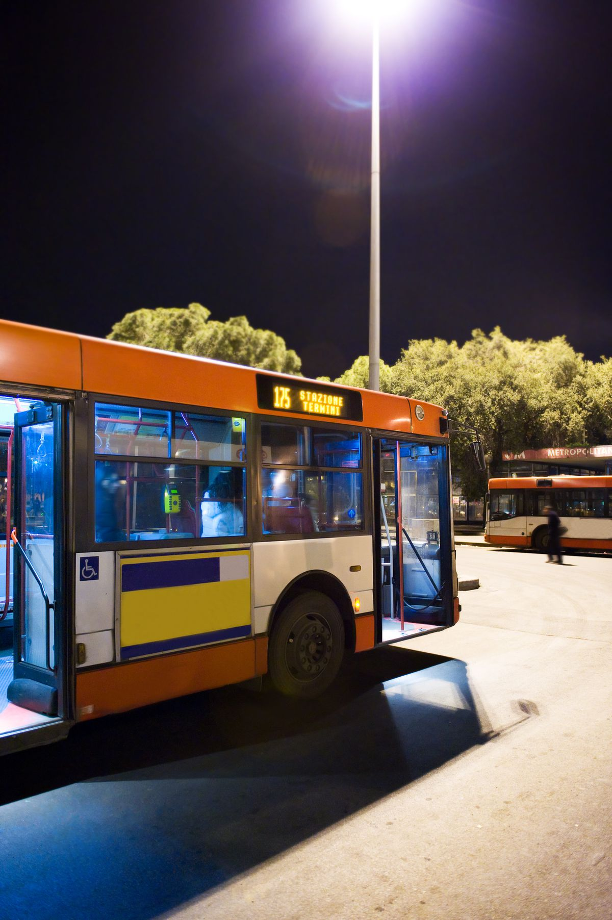 A orange bus pulls up to a station late at night.