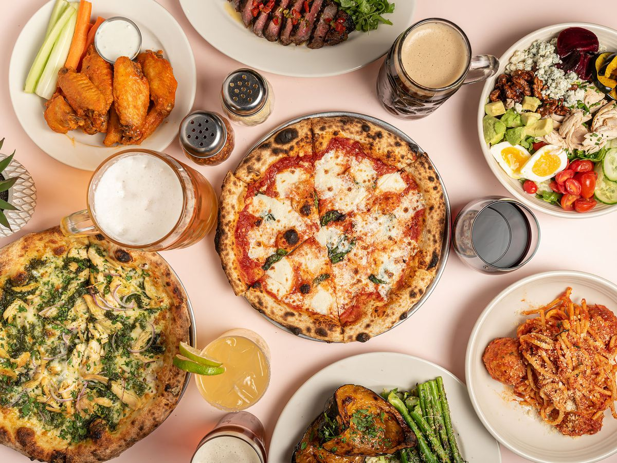A light pink table full of Italian food like pizzas and pasta.