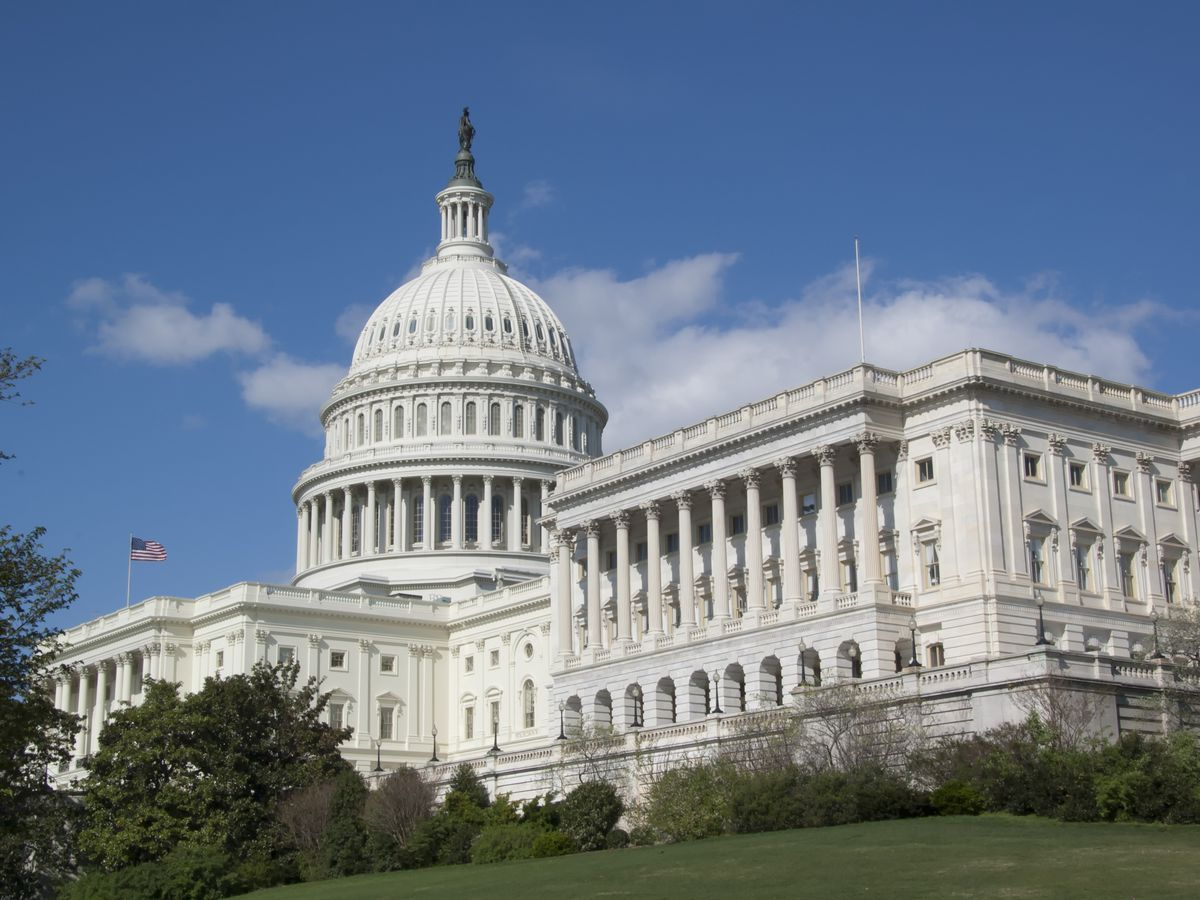 The exterior of the United States Capitol building. The facade is white with a domed roof and columns.