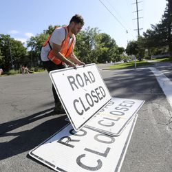 Layne Ferguson, a designer with Team Better Block, helps set up road closure signs before painting the intersection of 300 East and 700 South in Salt Lake City on Wednesday, Sept. 4, 2019. The Salt Lake City Mayor's Office, Spin and Bike Utah are partnering to turn the intersection into a multimodal community space.