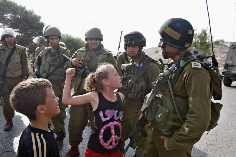 In this November 2, 2012, photo, then 12-year-old Ahed Tamimi tries to punch an Israeli soldier during a protest, in the West Bank village of Nabi Saleh.