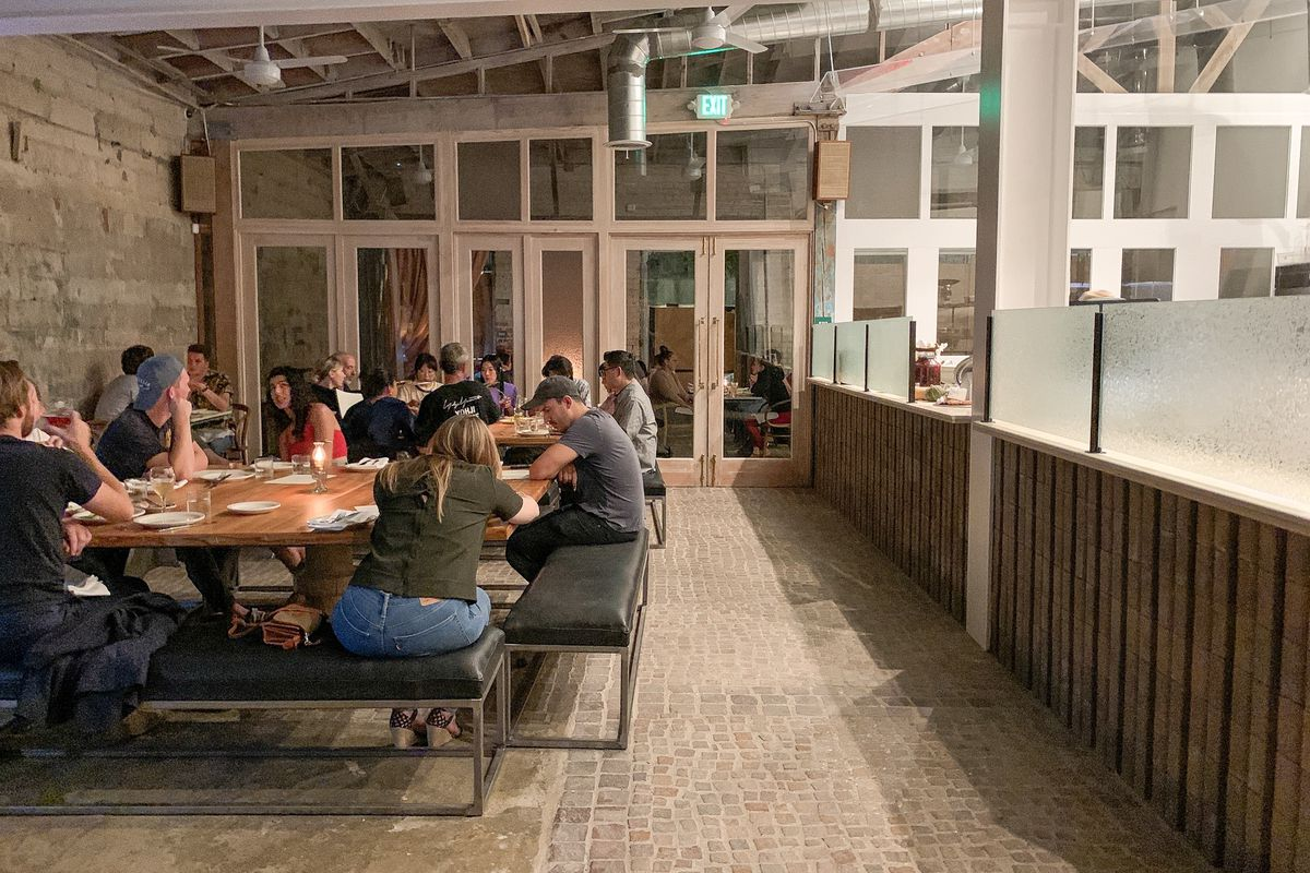 A hip pizza restaurant with customers and communal tables inside at night.