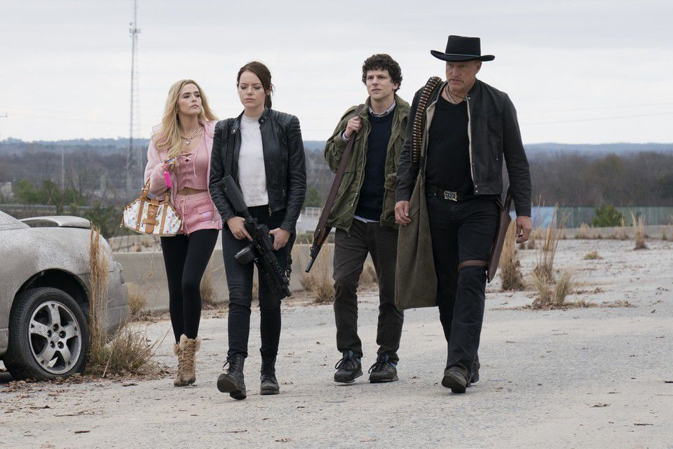 zombieland double tap stars emma stone, jesse eisenberg, and woody harrelson walk down the street with weapons in hand
