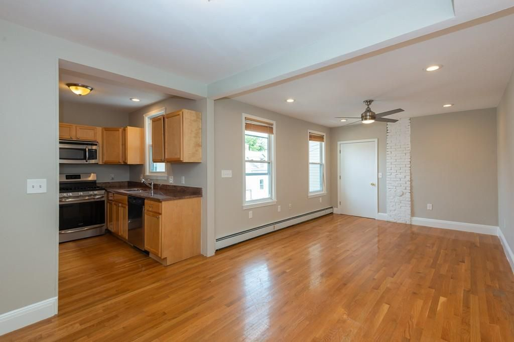 A large empty living room next to a kitchen alcove.