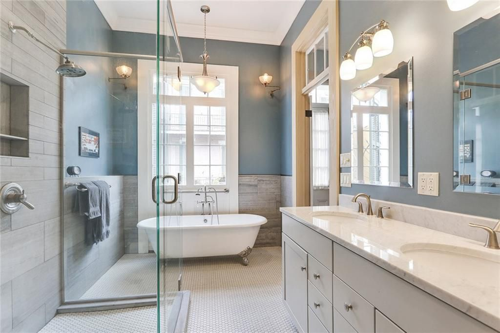 A tiled master bathroom has a glass walk-in shower on the left. a white clawfoot tub in the rear, and a white marble vanity with two sinks on the right.