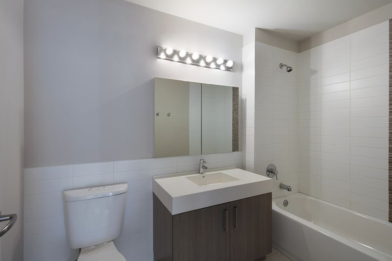 A bathroom with beige walls and white tiles.