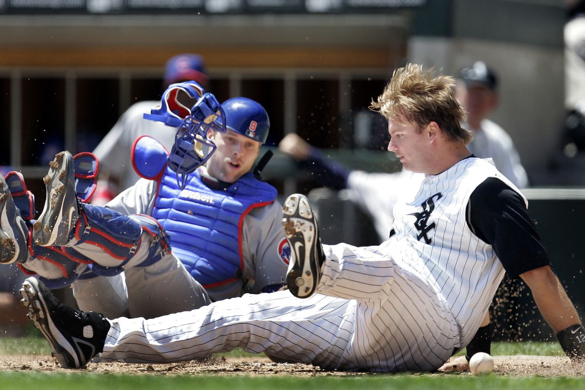 Chicago White Sox's A.J. Pierzynski, right, is safe at home after he collided with Chicago Cubs catcher Michael Barrett, left, during the second inning of a of a baseball game Saturday, May 20, 2006, in Chicago. After the play, Barrett punched Pierzynski resulting in a bench-clearing brawl. (AP Photo/Jeff Roberson) ORG XMIT: CXS105