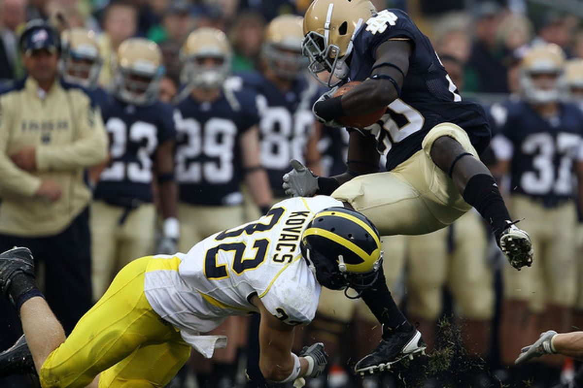 SOUTH BEND IN - SEPTEMBER 11: Cierre Wood #20 of the Notre Dame Fighting Irish is tackled by Jordan Kovacs #32 of the Michigan Wolverines at Notre Dame Stadium on September 11 2010 in South Bend Indiana. (Photo by Jonathan Daniel/Getty Images)