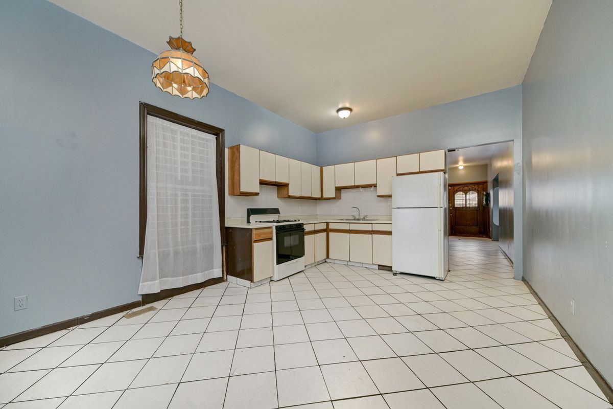 A roomy kitchen with white tiled floor. In one corner are wood cabinets with a white veneer.