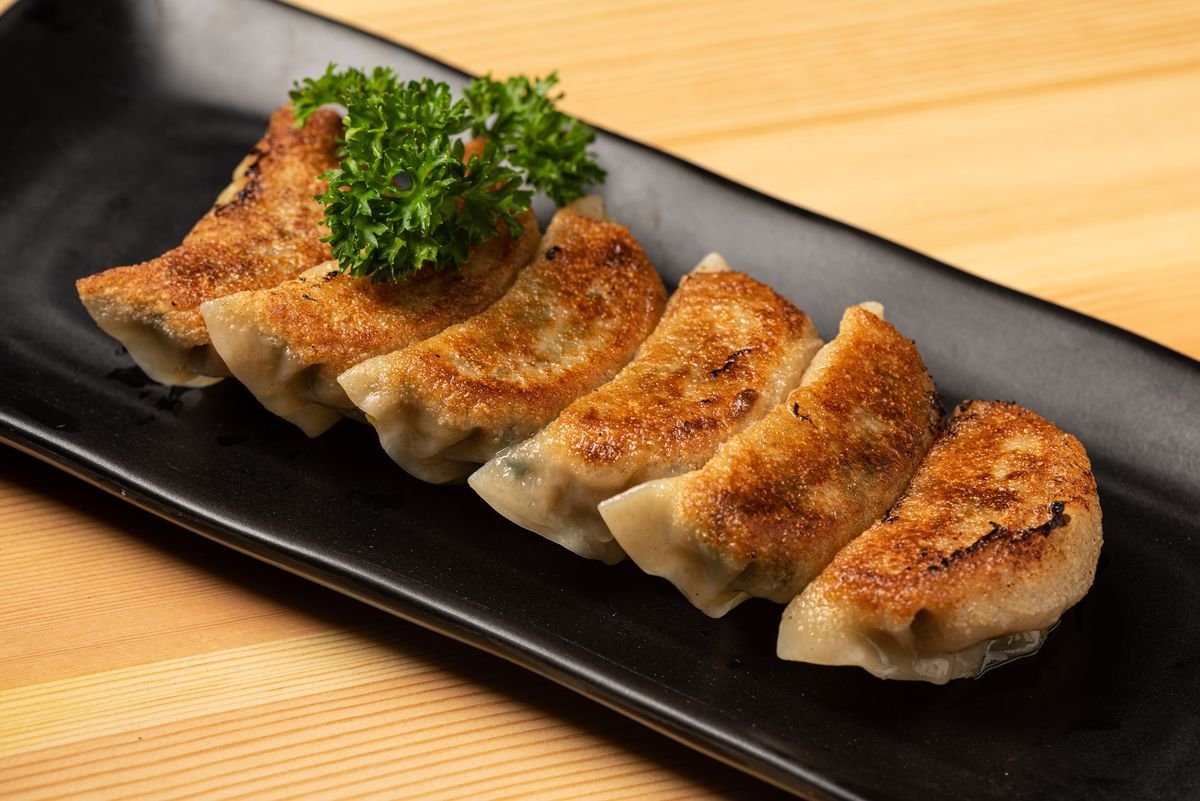 Beef, pork, and cabbage dumplings on a black plate with a green garnish.