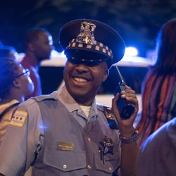 Chicago police officer Tatum stands at an intersection on 79th Street during the march. | Colin Boyle/Chicago Sun-Times