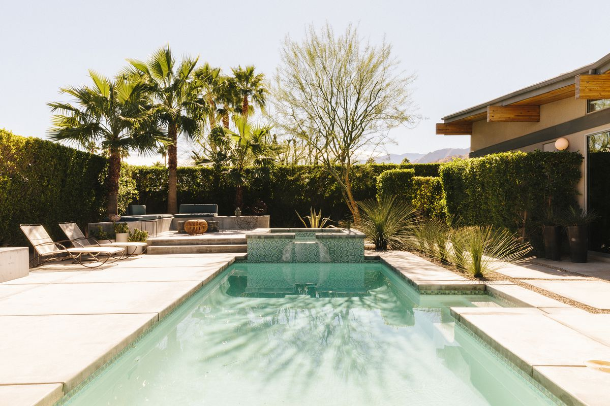 A swimming pool with aquamarine colored water. On one side of the pool is the exterior of a house. On the other side of the pool are lounge chairs. The yard is surrounded by palm trees and shrubbery.