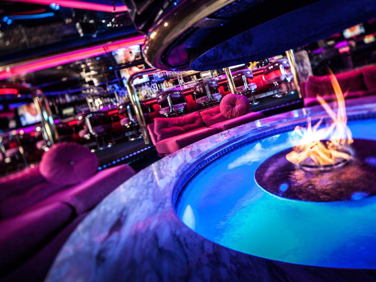 A neon-lit bar with a water feature with fire.