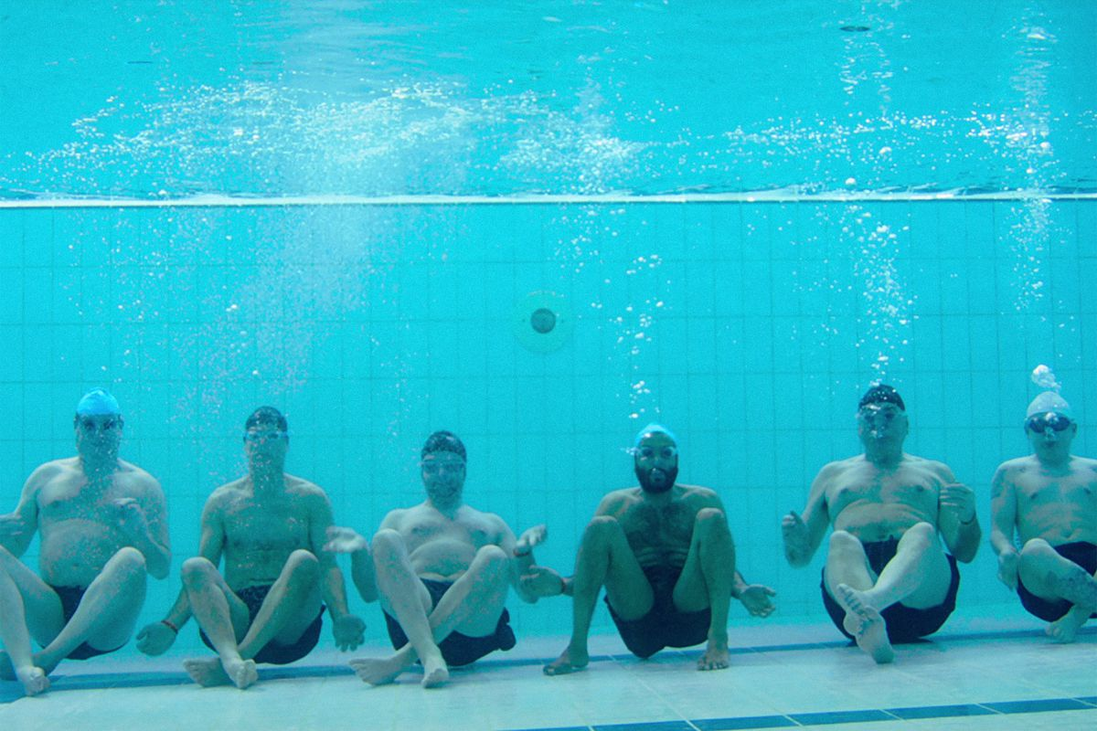 six men underwater in Swimming With Men