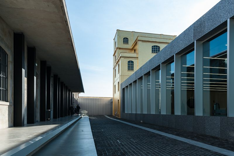 The exterior of Fondazione Prada in Milan. The facade features tall windows and terraced roofs.