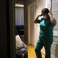 Nurse practitioner Capri Reese removes her face mask, sanitizes her shoes and put her scrubs in the washing machine before immediately showering at her South Loop apartment after a 12-hour shift at Roseland Community Hospital, where three patients suffering from COVID-19 died, Tuesday afternoon, April 28, 2020.
