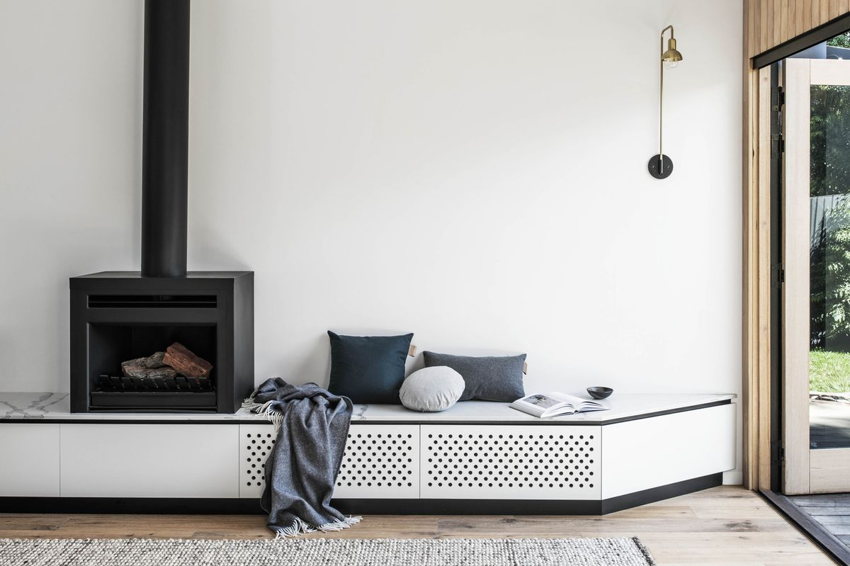 Electric stove in living room with built-in white seating.