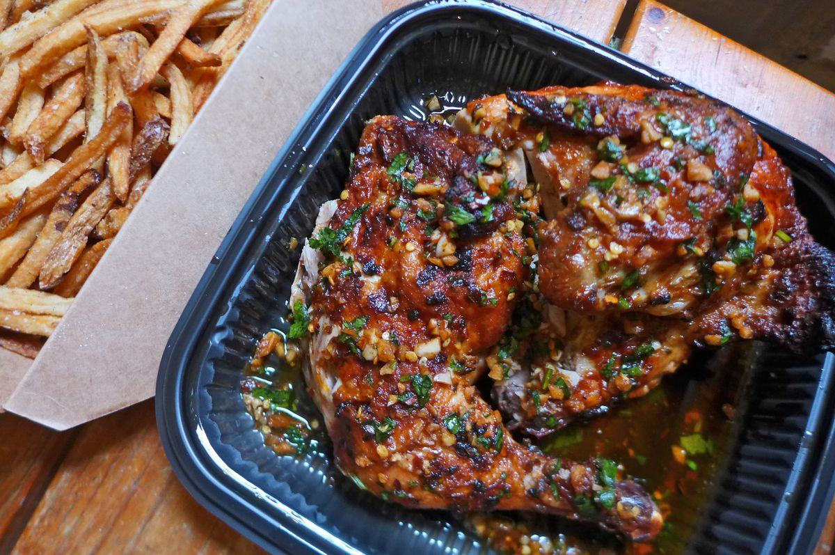 A roasted piece of chicken with brown and orange bits with some green herbs sprinkled on top and a plate of french fries placed on the side