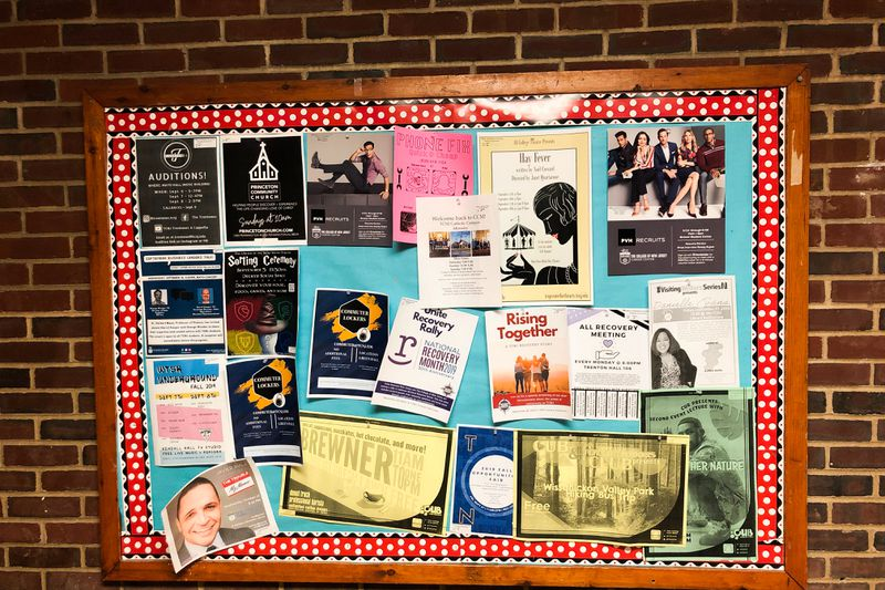 "A bulletin board with colorful posters advertising events like a ""recovery rally."""