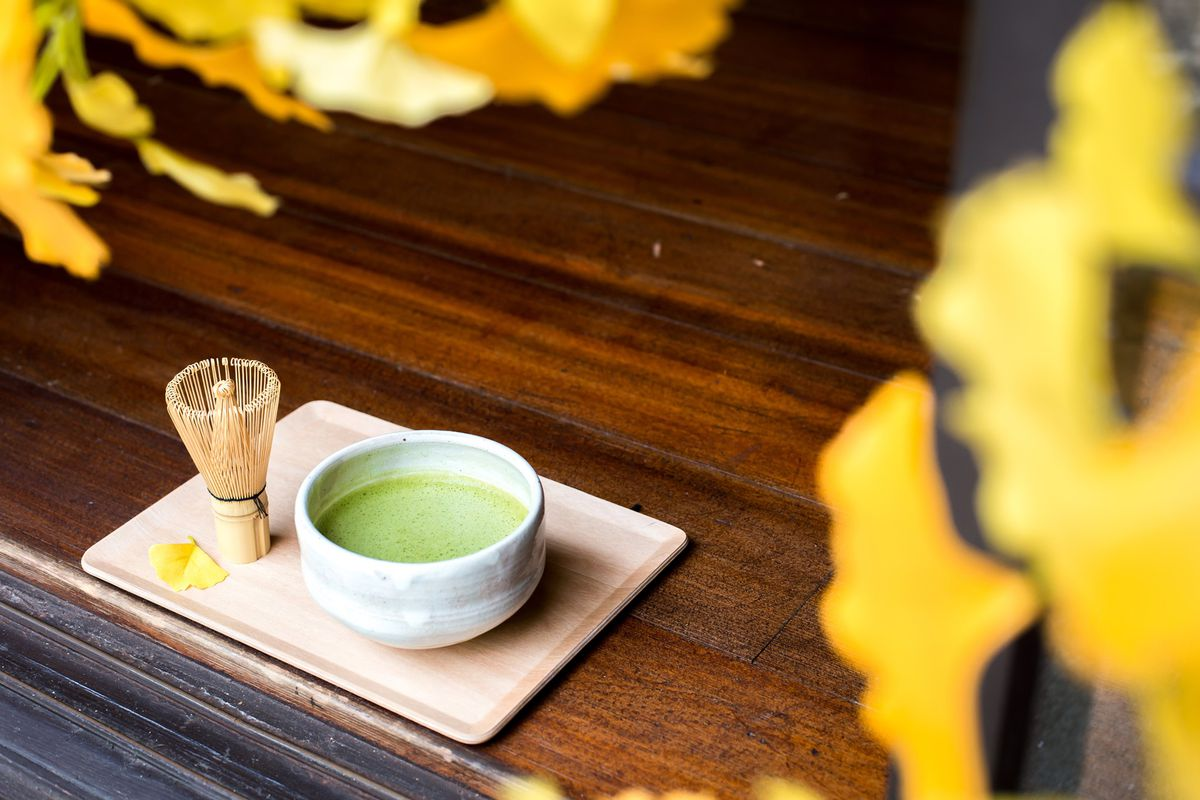 A cup of matcha on a wooden table.