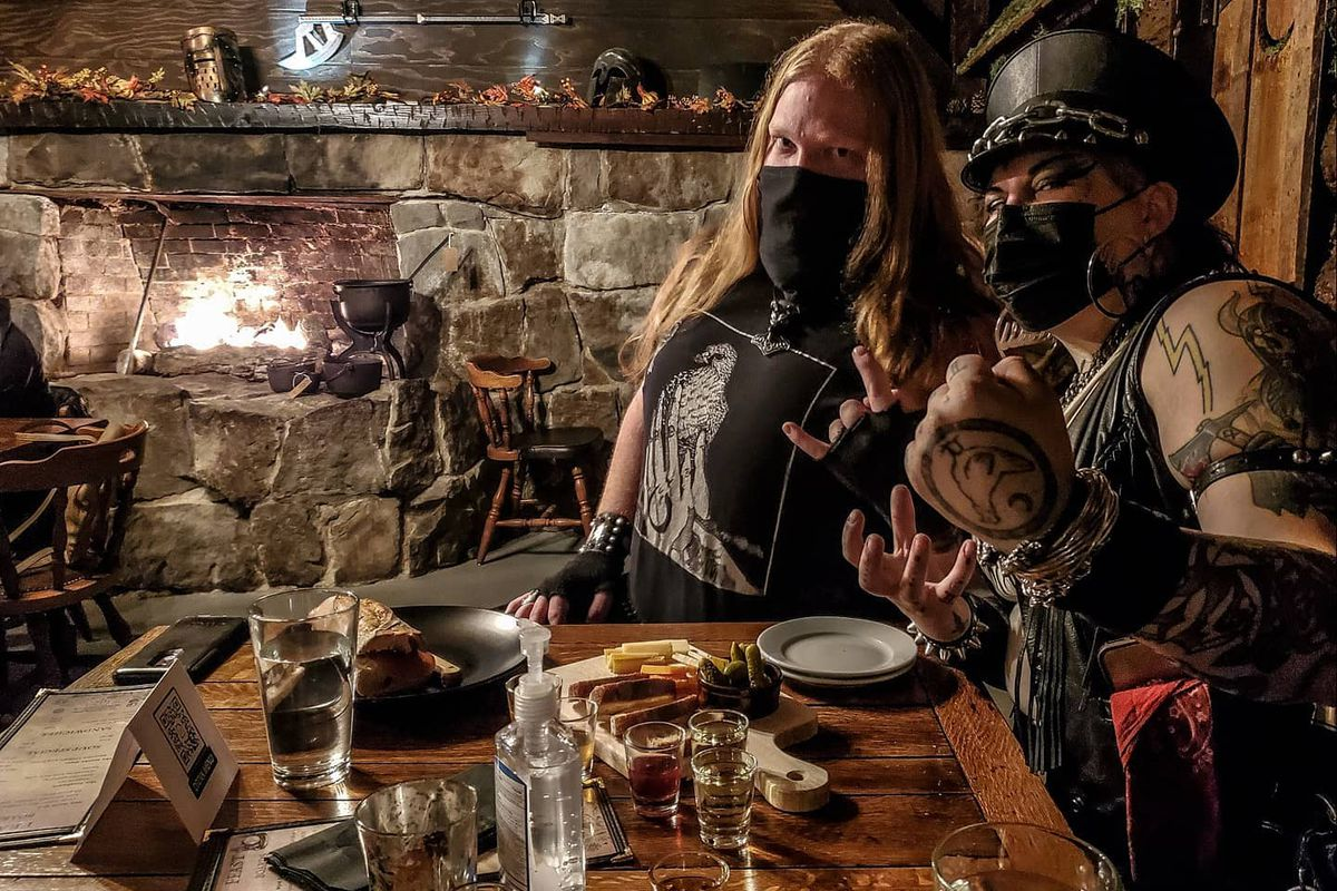 Two people at the table at Wyrd pose with food