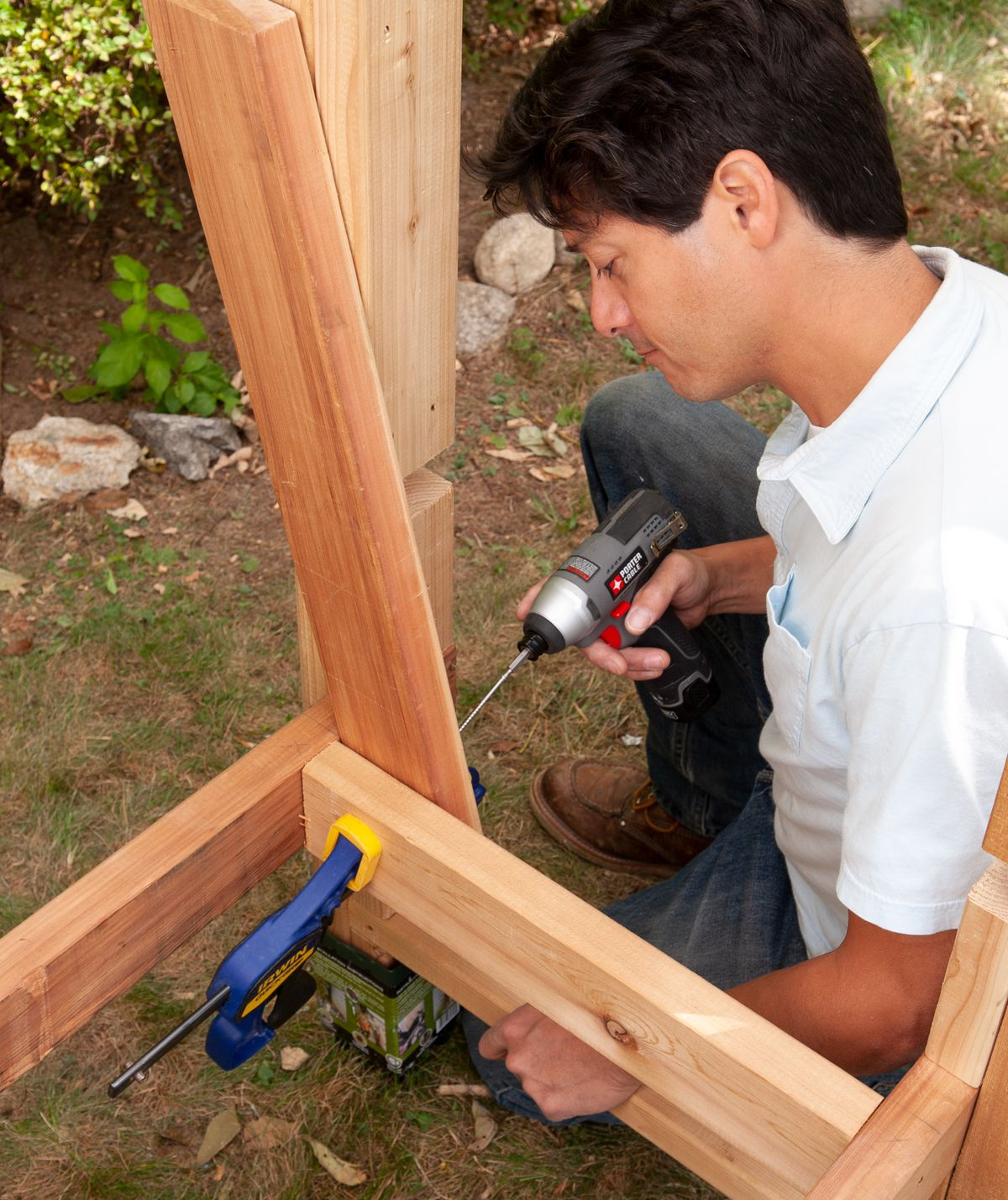 Man Cuts Pieces And Installs Side Supports Of Arbor Bench