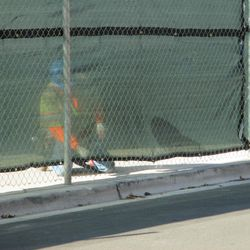 12:54 p.m. Workman securing the tarp, along the bottom of the Sheffield Avenue fence -