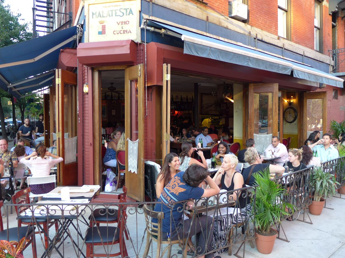 A corner storefront thrusts toward the viewer surrounded by outdoor tables on a fine summer day.