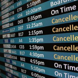 Signs at Salt Lake City International Airport show canceled flights due to a snowstorm, Thursday, Dec. 19, 2013.