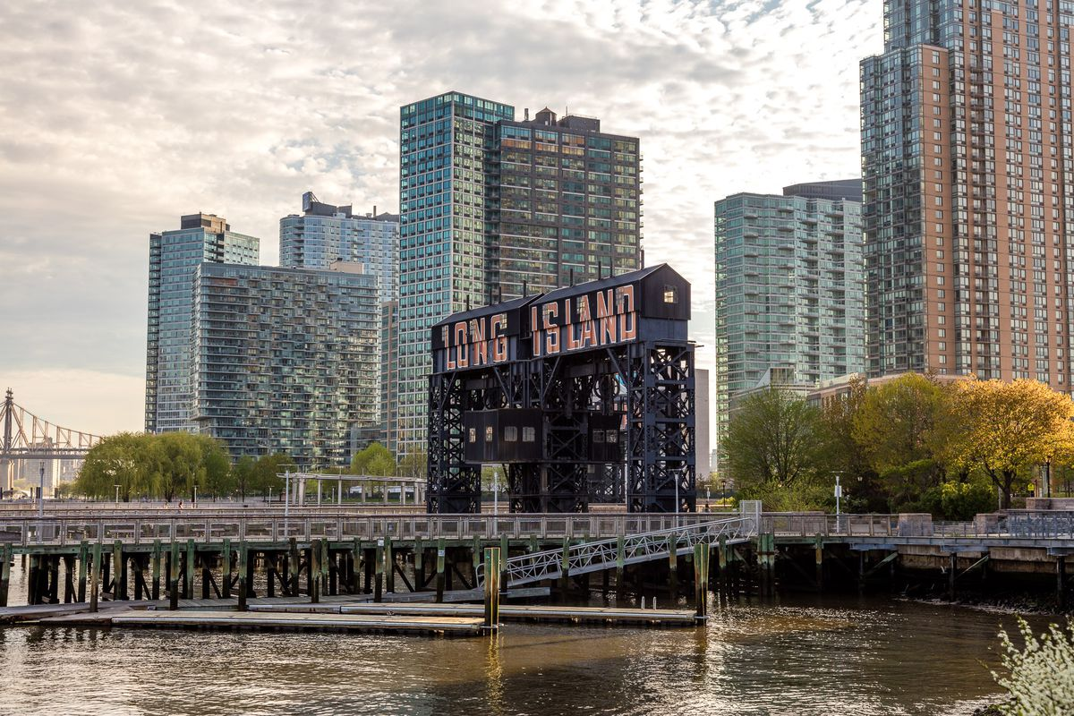 The waterfront in Long Island City. There is a pier with a sign that reads: Long Island. Behind the sign are many tall apartment buildings.