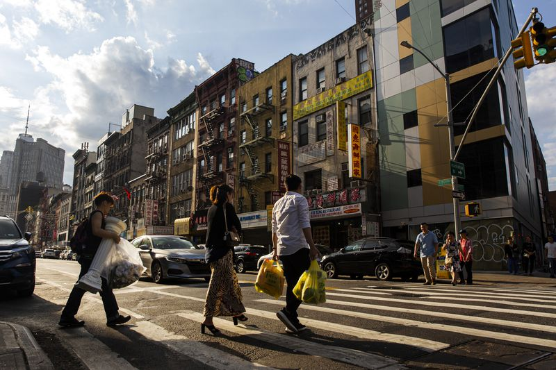 People carrying bags of groceries cross at a crosswalk in New York City's Chinatown.