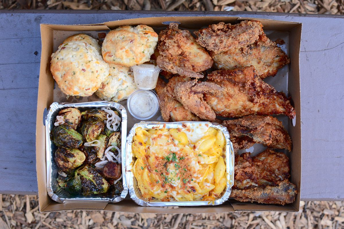 A box of fried chicken with biscuits, mac and cheese, and Brussels sprouts.