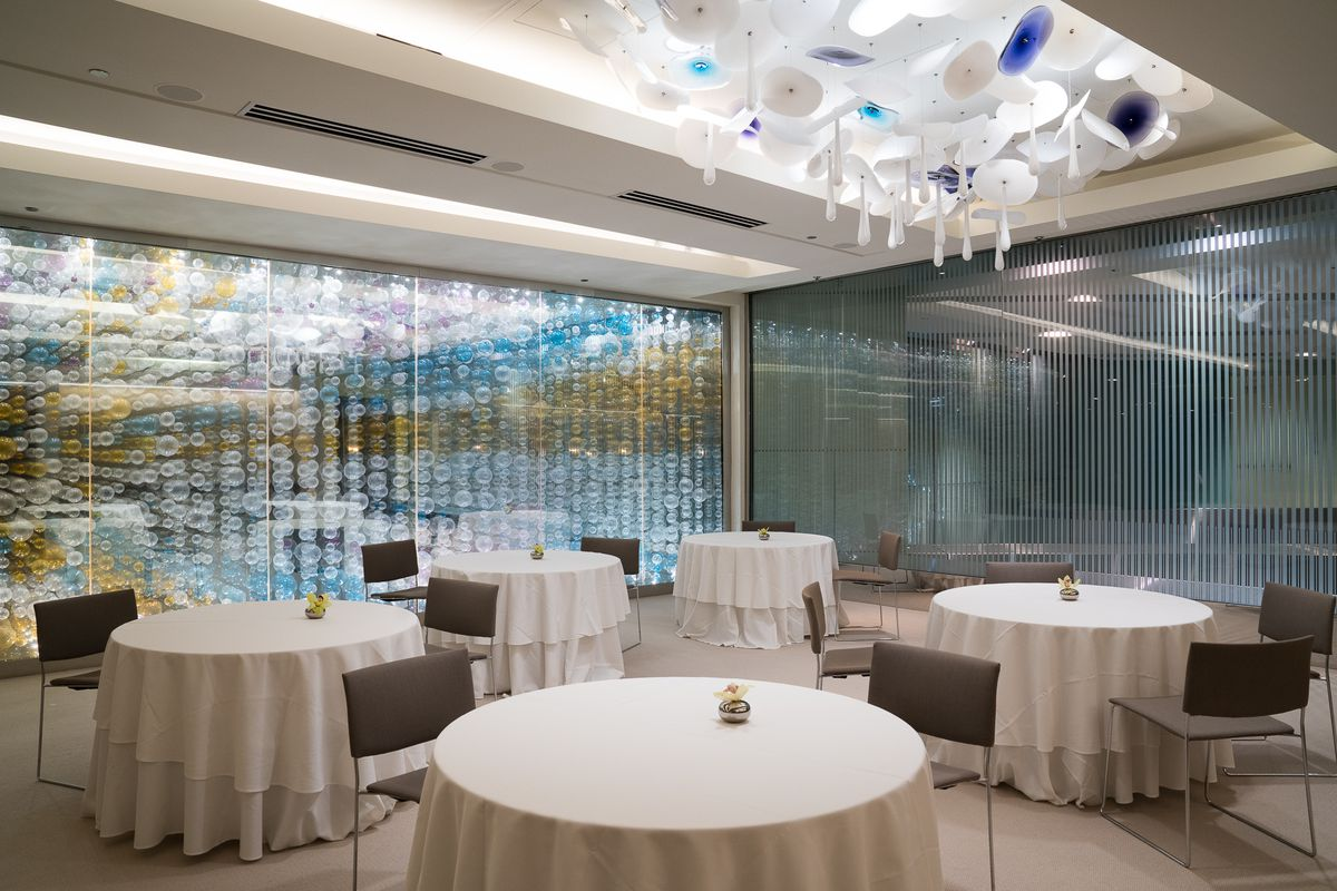 A brightly lit dining room with round tables with white tablecloths.