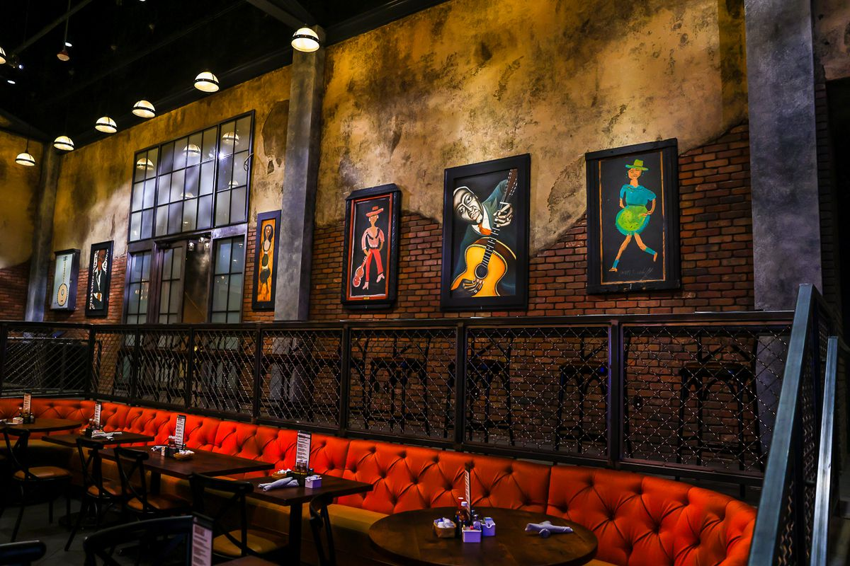 A red banquette with a table in front of a brown wall with artwork hanging on it at House of Blues