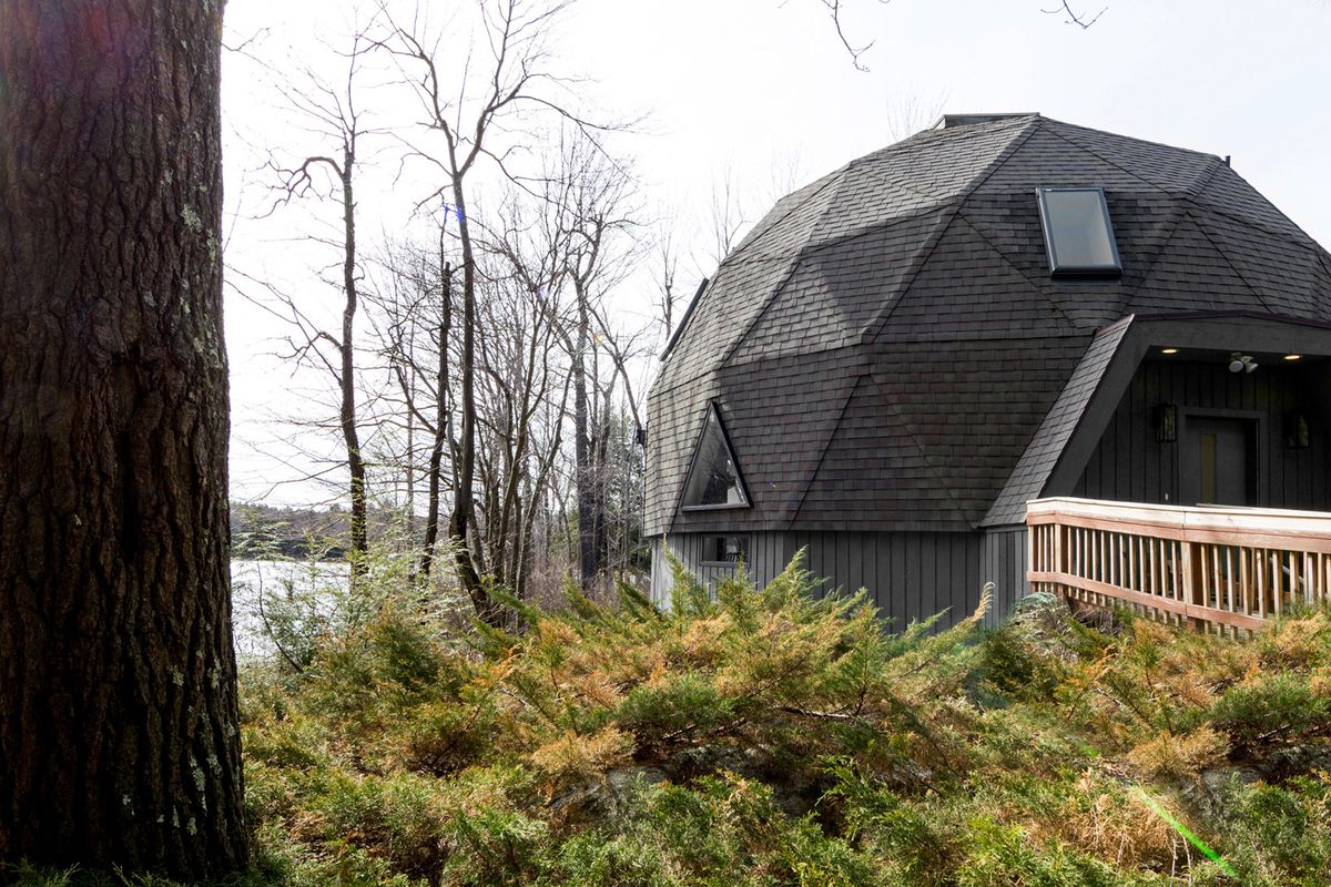 Geodesic dome home surrounded by greenery and a lake.