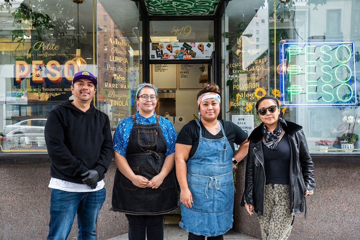A group of restaurant workers stands in front of their new restaurant in Downtown Los Angeles.