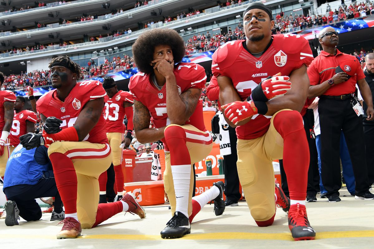 Eli Harold, Colin Kaepernick and Eric Reid of the San Francisco 49ers kneel on the sideline during the national anthem