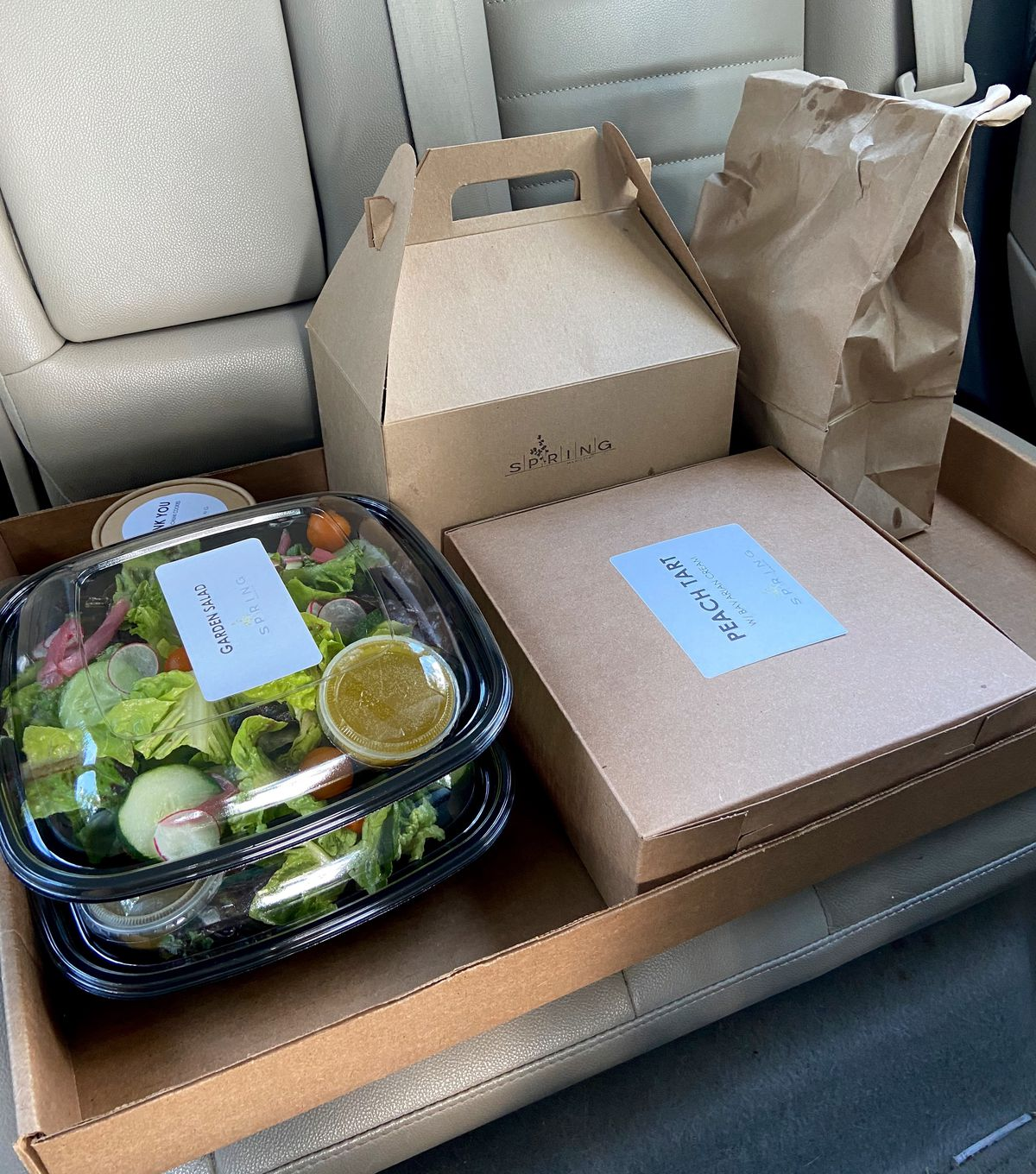 Takeout food boxed up and in the back seat of a car from Spring restaurant in Marietta, GA