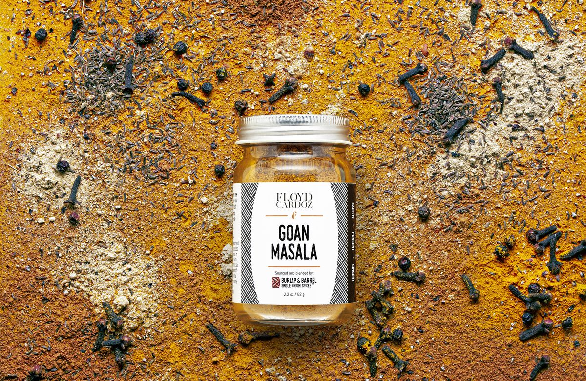 A jar of Goan masala laid against a background of the red orange spice blend scattered about