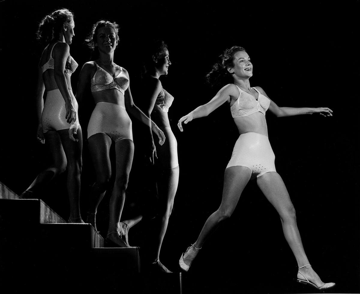 A woman clad in bra & Playtex panty girdle walking down steps.
