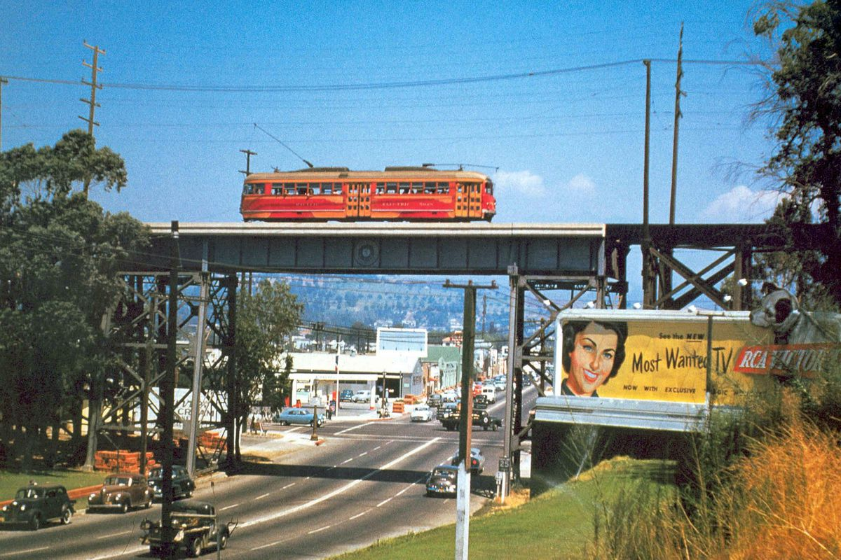 A red trolley car passing over a bridge above a roadway